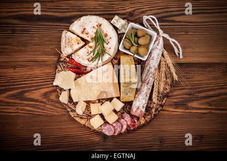 Cheese arrangement served on cutting board. Shot from aerial view - Stock Photo