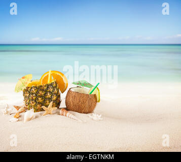 Sandy beach with fresh drinks in pineapple fruit - Stock Photo