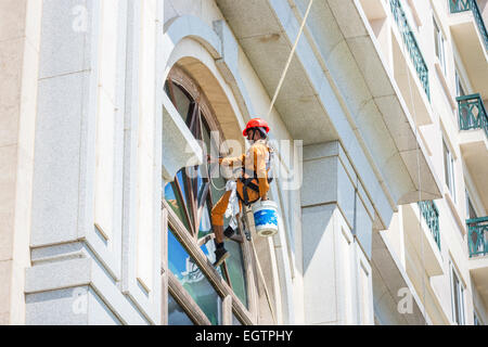 Window cleaner wearing orange overalls and red helmet, suspended from harness and ropes cleaning windows in Chennai, - Stock Photo