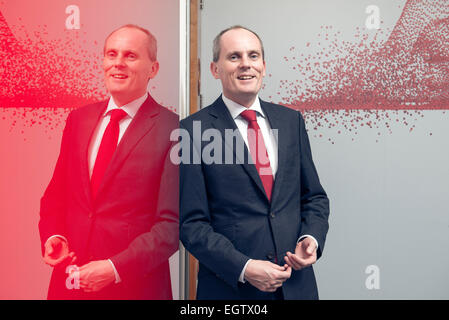 environmental portrait of businessman executive director in a suit lit in a creative way to imply technology & advancement - Stock Photo