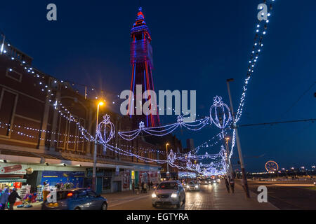 Cars in the promenade of Blackpool Illuminations at night with the illuminated tower - Stock Photo