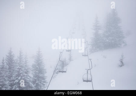 a skiers chairlift through the snowy mountains on a misty day in Kitzbuhel, Austria - Stock Photo