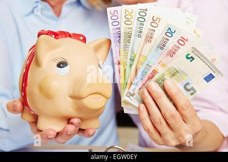 Two hands holding a piggy bank with Euro money bills - Stock Photo