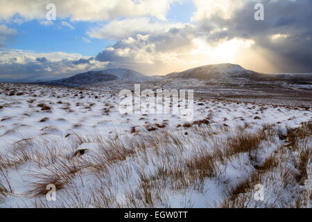 A low Winter Sun begins to set over Arenig Fach, Snowdonia. Arenig Fawr can be seen to the Left - Stock Photo