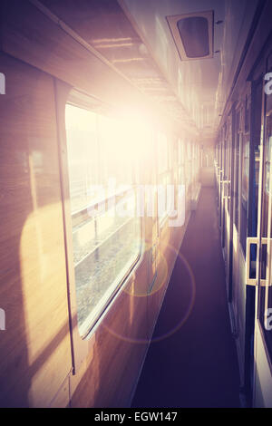 Retro filtered picture of a train coach interior with flare effect. - Stock Photo