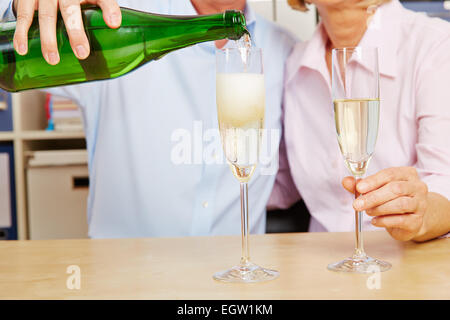 Old couple pouring champagne in glass for New Year's Eve - Stock Photo