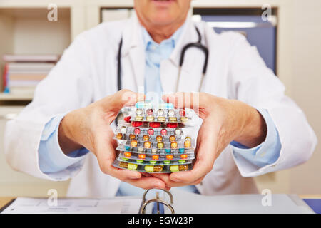Doctor holding many different colorful pills in in hands - Stock Photo