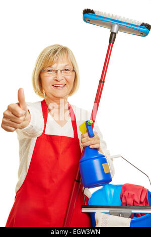 Happy cleaning lady holding thumbs up with many cleaning supplies in her hand - Stock Photo