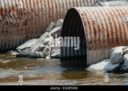 Rusted culvert pipe opening leading into brown water. - Stock Photo