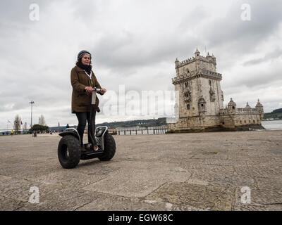 Female tourist riding a Segway sightseeing during a tour of the Torre de Belém (Belem Tower) area in Lisbon, Portugal, - Stock Photo