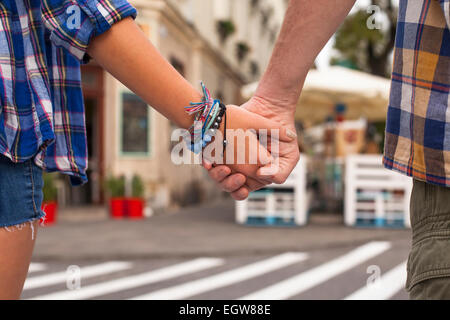Close-up of the holding hands of a young couple in a summer town. - Stock Photo
