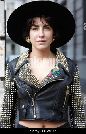 MILAN - FEBRUARY 26: Woman poses for photographers before show Milan Fashion Week Day 2, Fall/Winter 2015/2016 street - Stock Photo