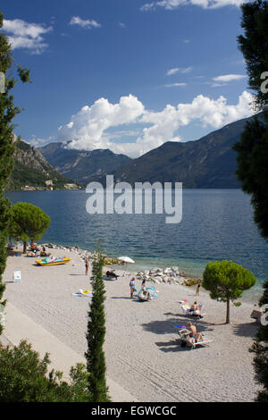 People relaxing on the beach at Limone sul Garda with views across Lake Garda to the mountains. - Stock Photo