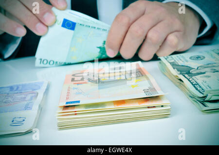 closeup of the hands of a young man who is counting euro banknotes on a table with some pile of pound, euro and - Stock Photo