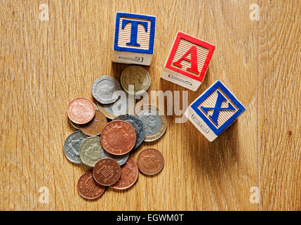 Wooden bricks spelling the word tax and English money cash coins finance business concept - Stock Photo