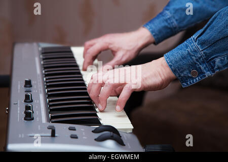 hands of the musician on the keyboard synthesizer - Stock Photo