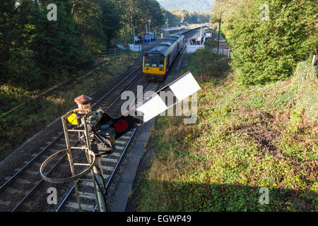 Northern Rail train approaching semaphore signal at clear on leaving Grindleford Railway Station, Derbyshire, Peak - Stock Photo