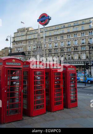 4 red British telephone boxes outside Charring Cross station, with an underground roundel also visible - Stock Photo