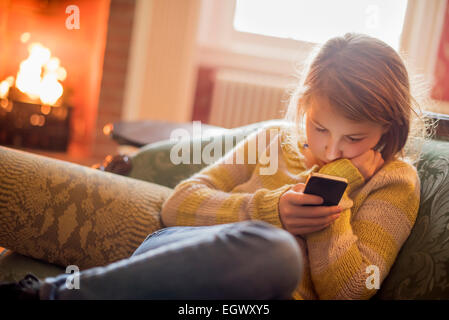 A young girl sitting checking her cell phone. - Stock Photo