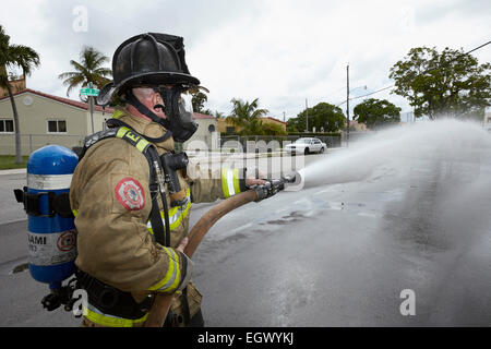 Firefighter with hose - Stock Photo