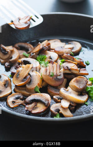 Butter fried sliced mushrooms with parsley in a pan. - Stock Photo