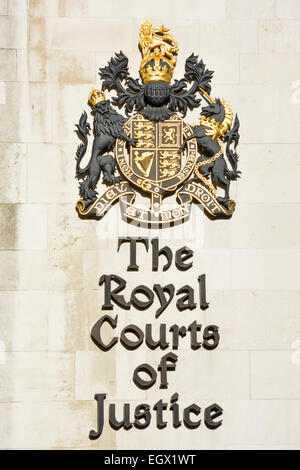 Royal Courts of Justice London & Royal Coat of arms of the United Kingdom as signs on the walls of the court building - Stock Photo