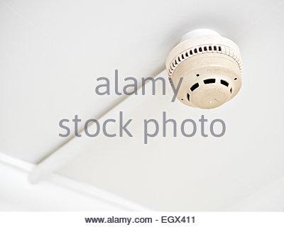 Smoke alarm detector in ceiling - Stock Photo