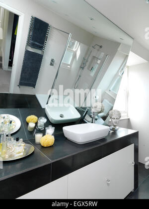Washbasin set on cupboard unit in bathroom, UK home - Stock Photo