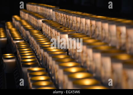Dramatic picture of a lot of burning candles in a row - Stock Photo