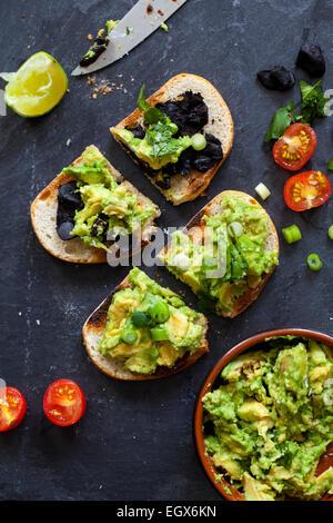 Canapes with avocado spread and black garlic - Stock Photo