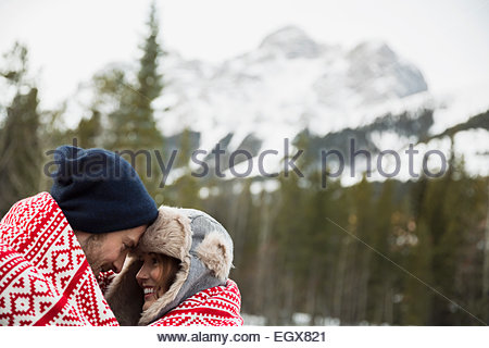 Couple wrapped in blanket below snowy mountain - Stock Photo