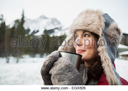 Woman in fur hat drinking hot cocoa outdoors - Stock Photo