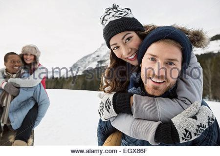 Portrait of hugging couple in snowy field - Stock Photo