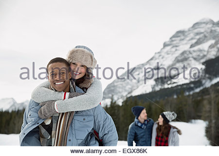Portrait of couple piggybacking in snowy field - Stock Photo