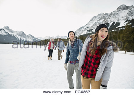 Couple holding hands in snowy field below mountains - Stock Photo
