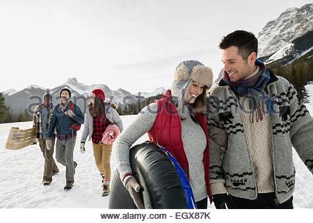 Friends walking in snowy field below mountains - Stock Photo