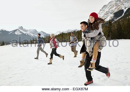Friends running in snowy field below mountains - Stock Photo