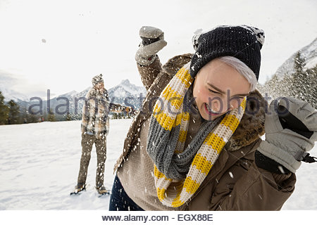 Couple enjoying snowball fight in field below mountains - Stock Photo