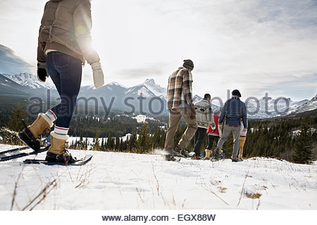 Friends snowshoeing below snowy mountains - Stock Photo