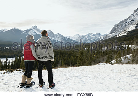 Couple snowshoeing and looking at snowy mountain view - Stock Photo