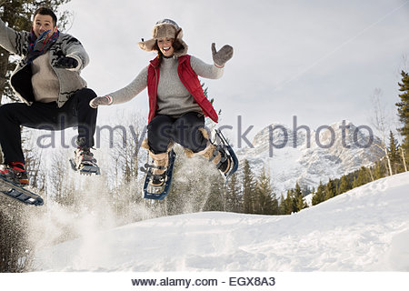 Couple jumping in snowshoes below snowy mountain - Stock Photo