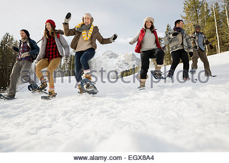 Enthusiastic friends snowshoeing below snowy mountain - Stock Photo