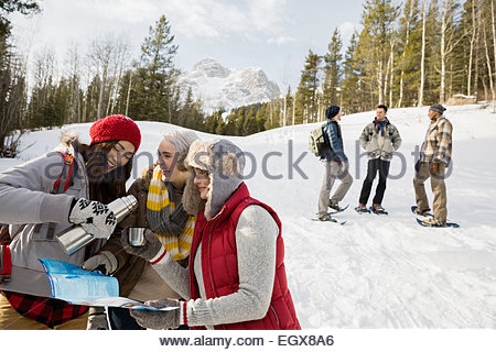 Friends drinking hot cocoa below snowy mountain - Stock Photo