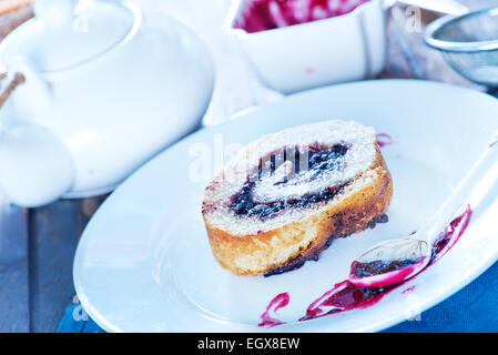sweet roll on plate and on a table - Stock Photo