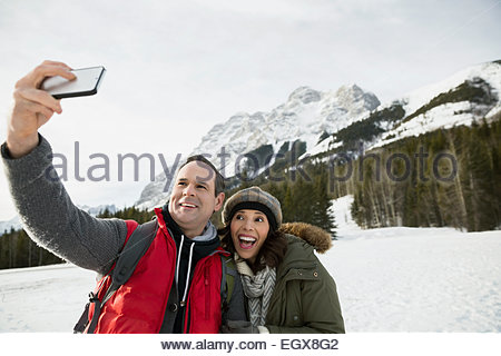 Couple taking selfie below snowy mountains - Stock Photo