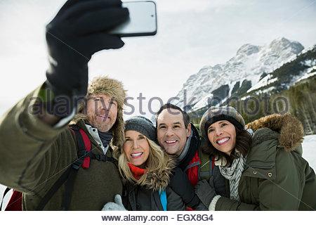Couples taking selfie below snowy mountains - Stock Photo