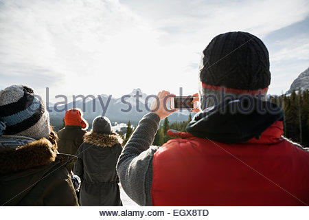 Man with camera phone photographing snowy mountains - Stock Photo