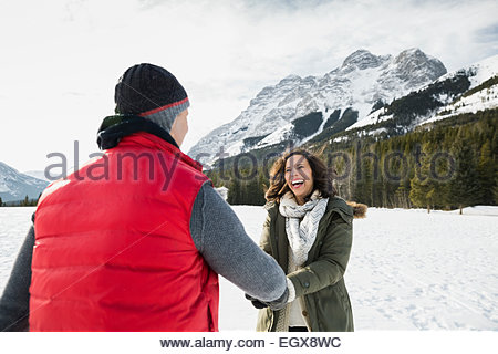 Smiling couple in snowy field below mountains - Stock Photo