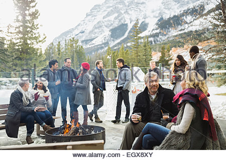 People drinking cocktails on patio below mountain - Stock Photo