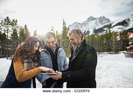 Friends using digital tablet on patio below mountains - Stock Photo